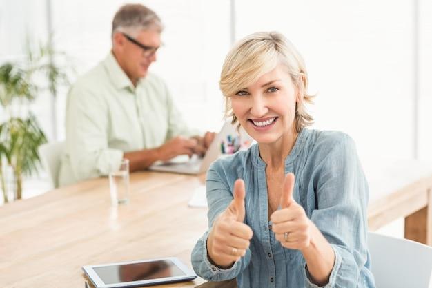 Uśmiechnięty bizneswoman gestykuluje aprobaty