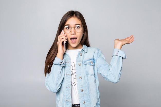 Uśmiechnięty bizneswoman opowiada na telefonie, odosobnionym na biel ścianie