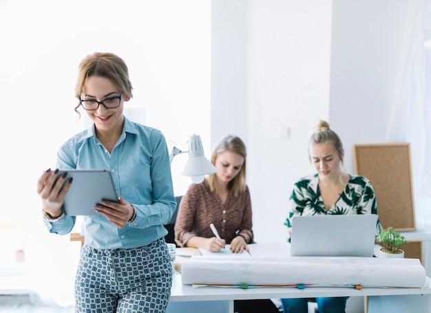 Uśmiechnięty bizneswoman patrzeje cyfrową pastylkę z jej kolegą pracuje przy tłem