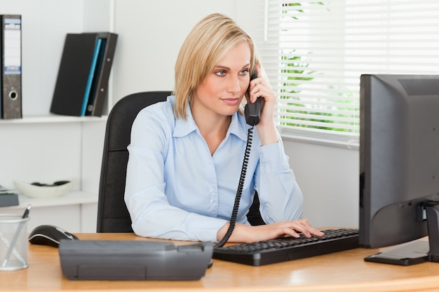Uśmiechnięty bizneswoman patrzeje jej ekran na telefonie