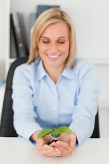 Uśmiechnięty bizneswoman patrzeje małej zielonej rośliny