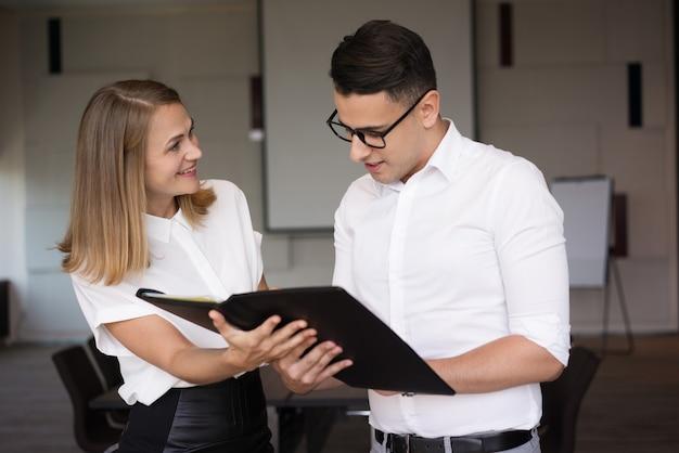 Uśmiechnięty bizneswoman pokazuje falcówkę z dokumentem biznesmen.