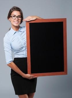 Uśmiechnięty bizneswoman pokazuje pustą tablicę