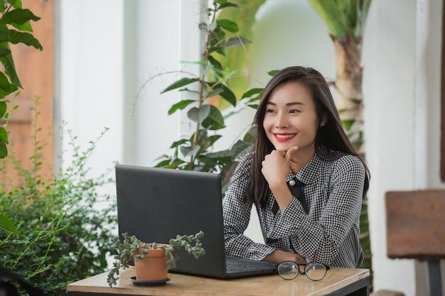 Uśmiechnięty bizneswoman pracuje na laptopie w kawiarni