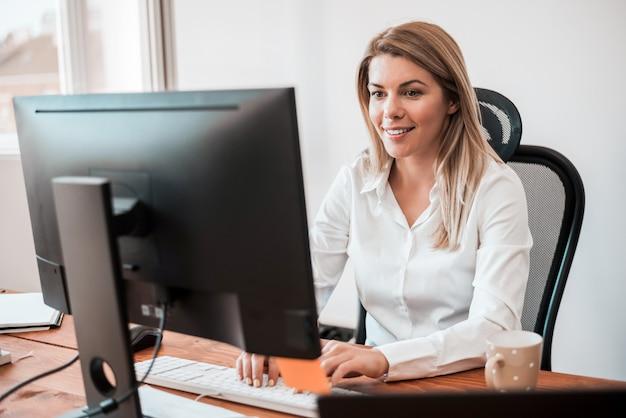 Uśmiechnięty bizneswoman pracuje przy biurka biurem.