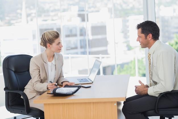 Uśmiechnięty bizneswoman przeprowadza wywiad biznesmena