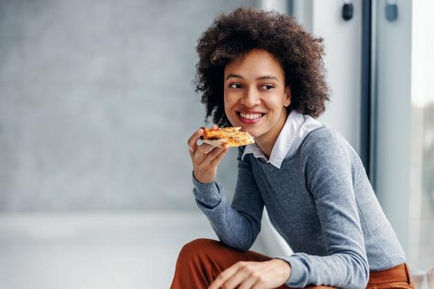 Uśmiechnięty bizneswoman rasy mieszanej siedzi i ma pizzę podczas przerwy na lunch.