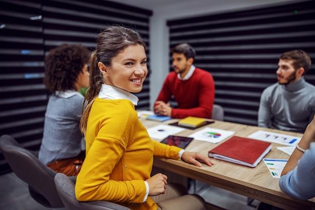 Uśmiechnięty bizneswoman siedzi w biurze z kolegami