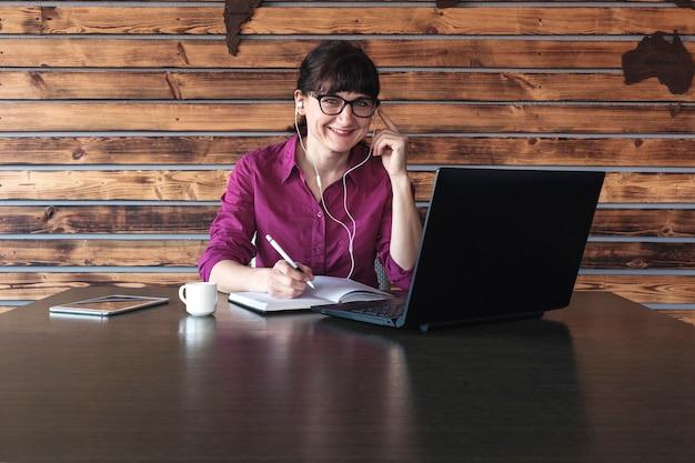 Uśmiechnięty bizneswoman słucha muzyka przy pracą
