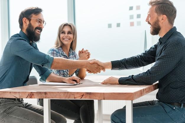 Uśmiechnięty bizneswoman uścisk dłoni ze swoim partnerem biznesowym