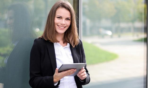 Uśmiechnięty bizneswoman używa cyfrową pastylkę plenerową