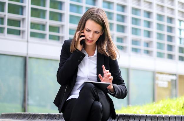 Uśmiechnięty bizneswoman używa cyfrowej pastylki plenerowego obsiadanie na ławce i mówienie na telefonie
