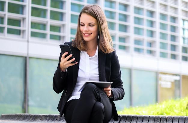 Uśmiechnięty bizneswoman używa cyfrowej pastylki plenerowego obsiadanie na ławce i susing także jej smartphone
