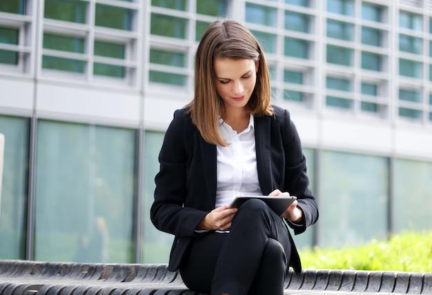 Uśmiechnięty bizneswoman używa cyfrowej pastylki plenerowego obsiadanie na ławce