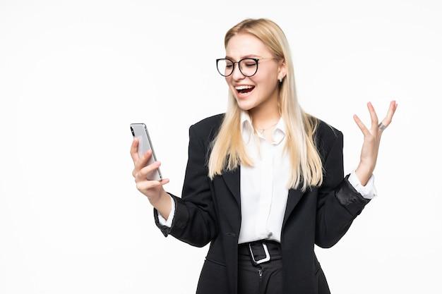 Uśmiechnięty bizneswoman używa smartphone nad szarości ścianą.
