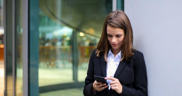 Uśmiechnięty bizneswoman używa smartphone plenerowego