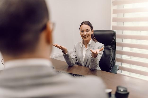 Uśmiechnięty bizneswoman w wizytowym siedzi w biurze i mówi do pracownika. dobry lider sprawia, że każdy chce dołączyć do swojego zespołu.