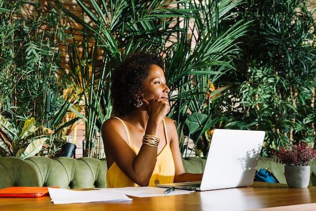 Uśmiechnięty bizneswoman z laptopem i dokumentem na drewnianym stole w restauraci