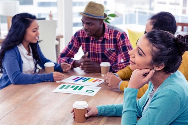 Uśmiechnięty bizneswomanu dzień marzy z kolegami dyskutuje przy kreatywnie biurem