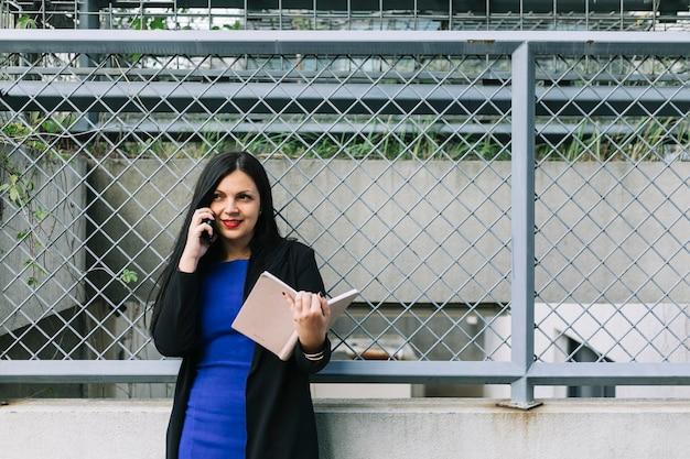 Uśmiechnięty bizneswomanu mienia dzienniczek i opowiadać na telefonie komórkowym
