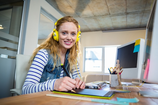 Uśmiechnięty bizneswomanu obsiadanie przy jej słuchającą muzyką i biurkiem
