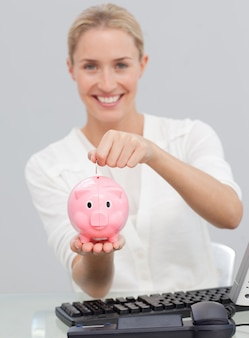 Uśmiechnięty bizneswomanu oszczędzania pieniądze w piggibank