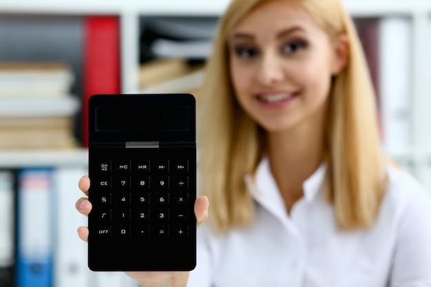Uśmiechnięty bizneswomanu portret trzyma kalkulatora w ręce