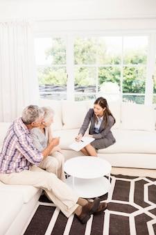 Uśmiechnięty bizneswomanu seansu dokumenty starsza para w żywym pokoju
