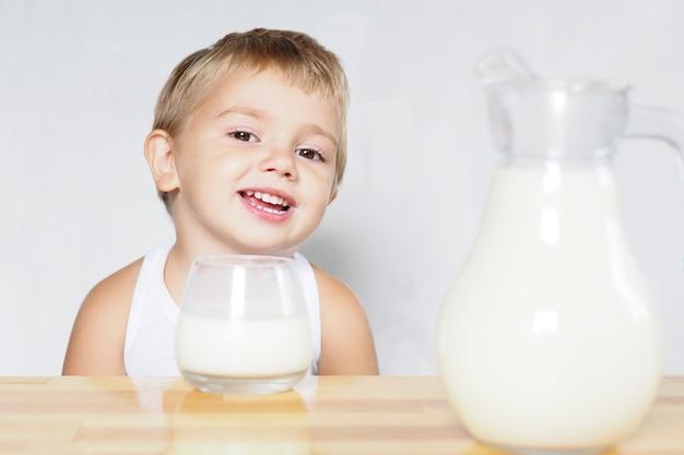 Uśmiechnięty blond chłopiec o brązowych oczach pije mleko ze szklanki przy drewnianym stole na białym tle.