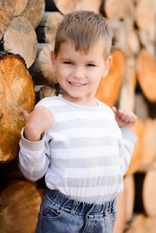 Uśmiechnięty blond chłopiec pokazuje kciuk stojący na drewnianym tle