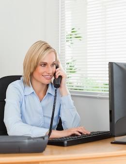 Uśmiechnięty blondynka bizneswoman patrzeje jej ekran w telefonie