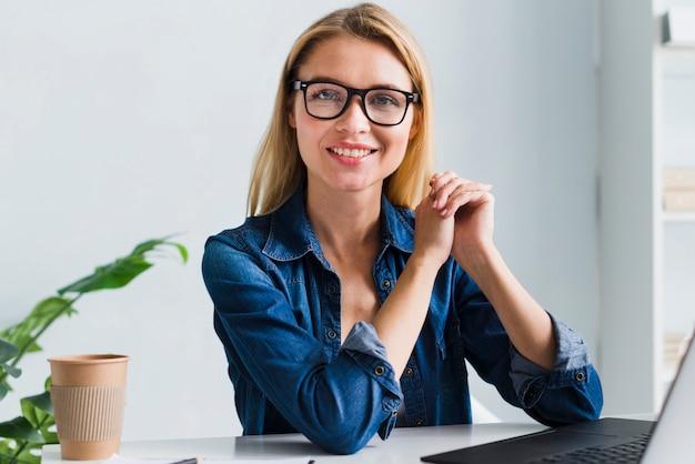 Uśmiechnięty blondynka pracownik patrzeje kamerę z szkłami