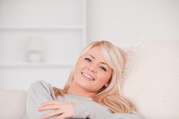 Uśmiechnięty blondynki kobiety lying on the beach na kanapie