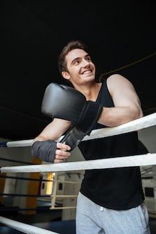 Uśmiechnięty bokser jest ubranym bokserskie rękawiczki i patrzeje daleko od