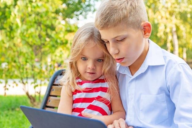 Uśmiechnięty brat i siostra siedzi na ławce w parku i bawić się na laptopie