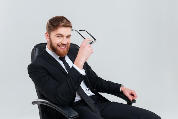 Uśmiechnięty brodaty biznesmen w czarnym garniturze ściąga okulary