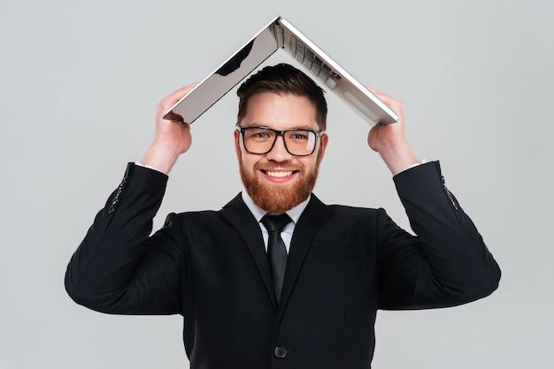 Uśmiechnięty brodaty biznesmen w okularach i garniturze, trzymający laptopa nad głową