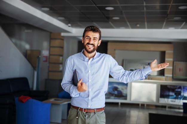Uśmiechnięty, brodaty ceo stojący w holu firmy przewozowej, trzymający tablet i gestykulujący, że dostawa jest na czas i wszystko idzie dobrze