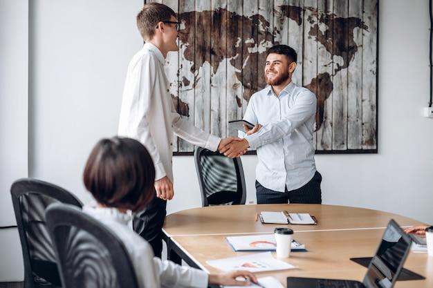 Uśmiechnięty brodaty chłopiec podaje rękę kolegi w biurze