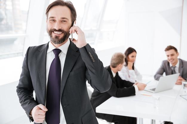 Uśmiechnięty brodaty człowiek biznesu rozmawia przez telefon w biurze z kolegami