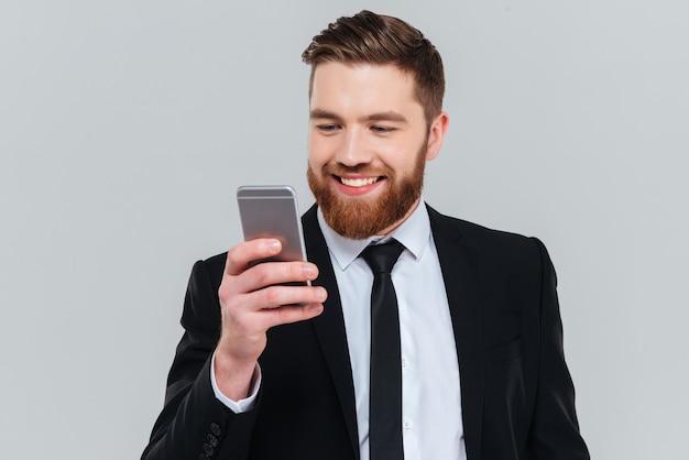 Uśmiechnięty brodaty człowiek biznesu w czarnym garniturze pisania wiadomości na telefonie w studio na białym tle szarym tle