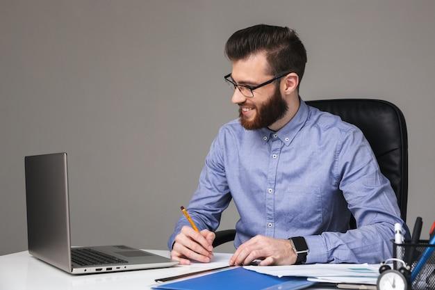 Uśmiechnięty brodaty elegancki mężczyzna w okularach, korzystający z laptopa i piszący coś, siedząc przy stole w biurze