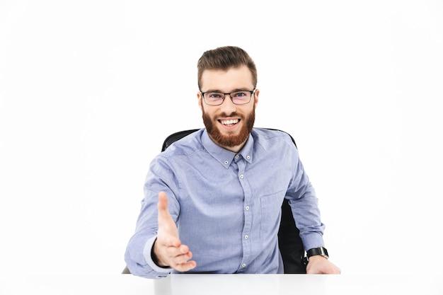 Uśmiechnięty brodaty elegancki mężczyzna w okularach na spotkaniu siedzący przy stole na szarym tle