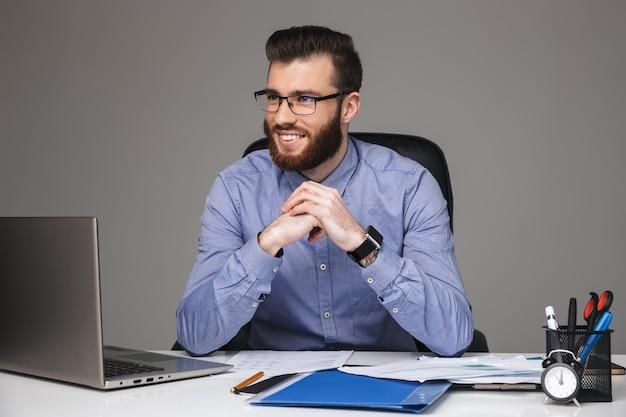 Uśmiechnięty brodaty elegancki mężczyzna w okularach odwracający wzrok, siedząc przy stole w biurze