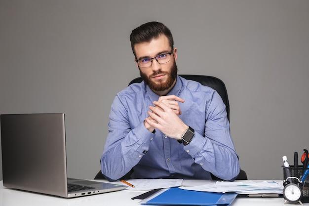 Uśmiechnięty brodaty elegancki mężczyzna w okularach, patrzący bezpośrednio, siedząc przy stole w biurze