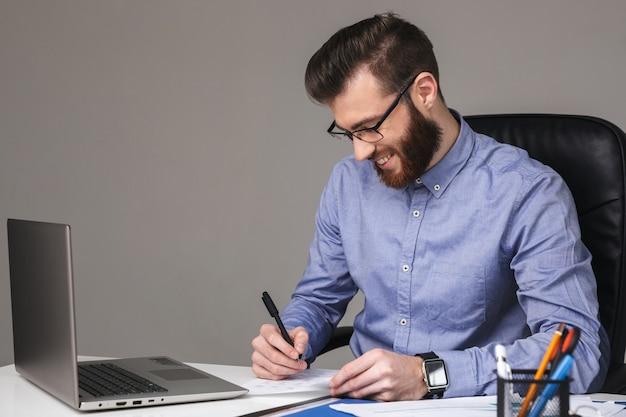 Uśmiechnięty brodaty elegancki mężczyzna w okularach pisze coś siedząc przy stole z laptopem w biurze