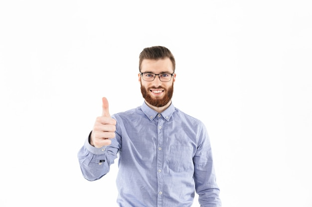 Uśmiechnięty brodaty elegancki mężczyzna w okularach pokazujący kciuk do góry i patrzący