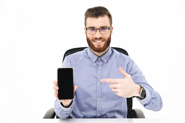 Uśmiechnięty brodaty elegancki mężczyzna w okularach pokazujący pusty ekran smartfona i wskazujący na niego, siedząc przy stole