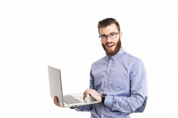Uśmiechnięty brodaty elegancki mężczyzna w okularach trzymający laptopa i patrzący i patrzący