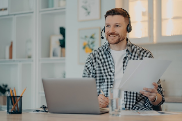 Uśmiechnięty brodaty facet siedzący w miejscu pracy i trzymający dokumenty podczas spotkania online, mężczyzna freelancer pracujący w domu i używający laptopa, noszący zestaw słuchawkowy. praca zdalna i koncepcja niezależnego strzelca